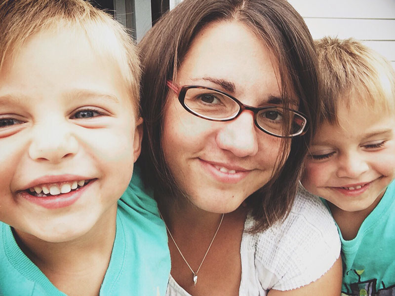 A woman who knows all about these tips for dating a single mom smiling with her two sons in her backyard.