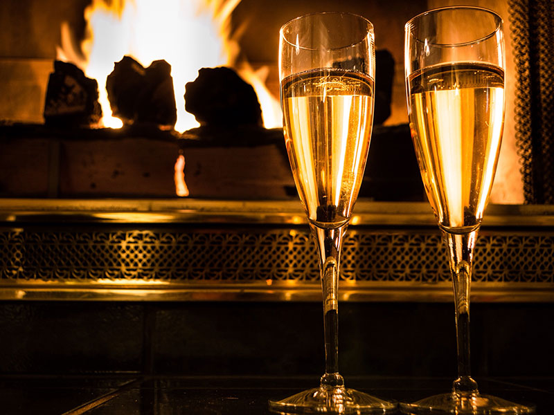 Two champagne glasses in front of a fire, one of these at home date night ideas.