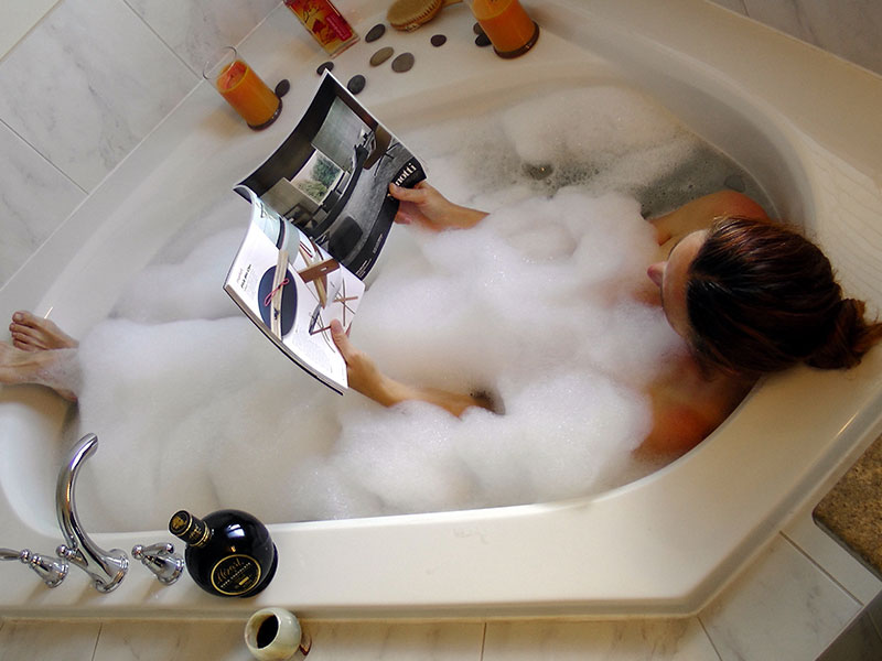 A woman in a bathtub reading a magazine in a bubble bath relaxing.