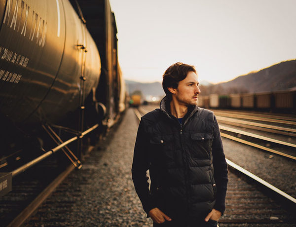 A sigma male walking by himself down some railroad tracks looking pensive.
