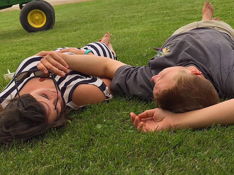 "A woman lying the grass with her friend, thinking to herself, ""I'm in love with my best friend."""