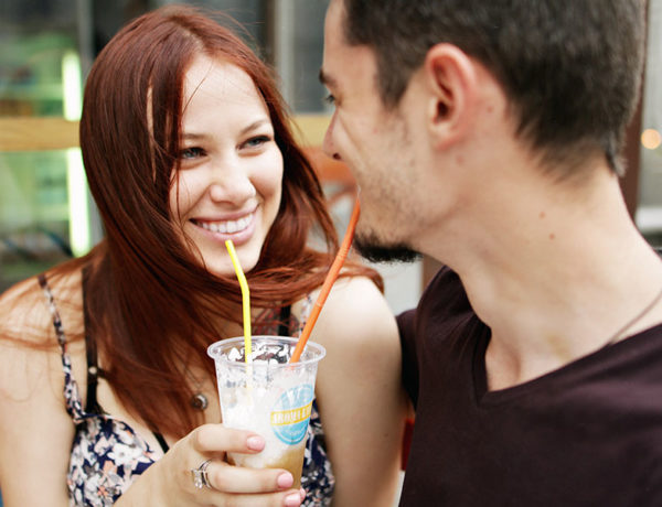 A man wondering what women want in a man, sharing a drink with his girlfriend as she smiles at him.