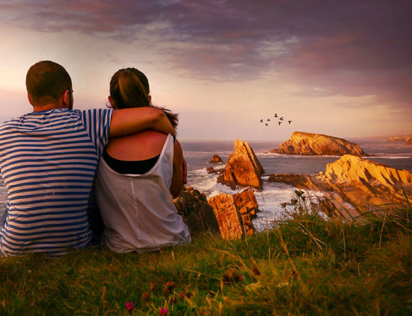 A couple who used on of these first date ideas, sitting on top of a hill looking at the sunset after a hike.