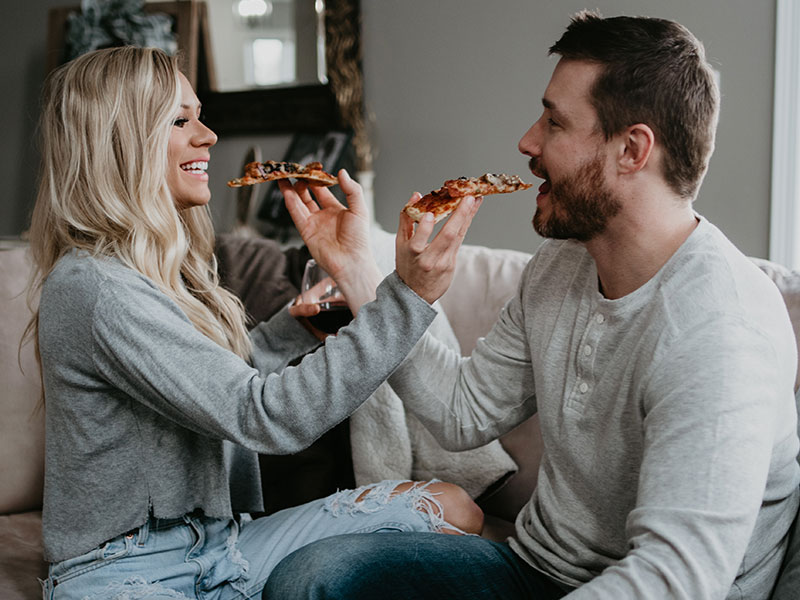 A couple using one of these cheap date night ideas and sharing pizza at home on the couch.