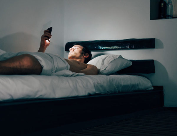 A guy in bed at night going through his Tinder top picks.
