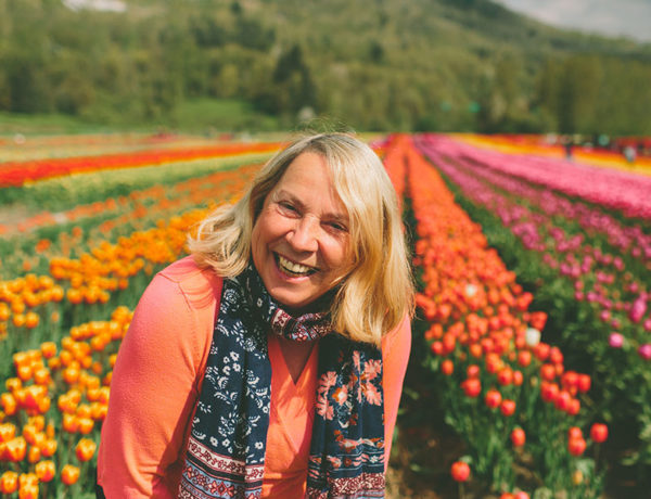 A woman who's learning how to get over a divorce laughing in a field of tulips.