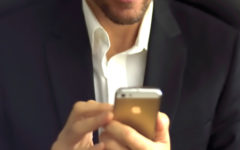 A guy double texting a girl and showing how guys text when they like you while wearing a nice suit and smiling.