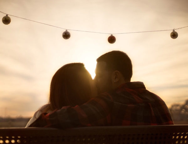 A man that learned how to love someone, kissing his significant other in front of the a sunset.