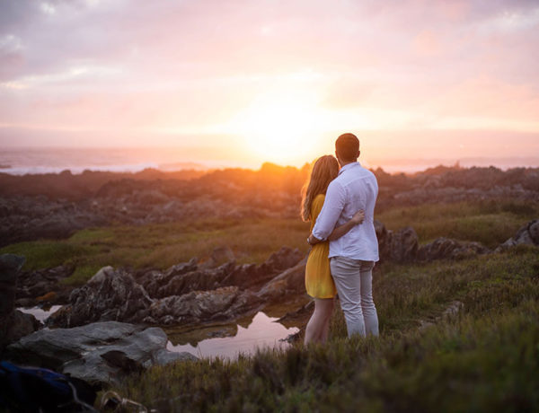 A woman wondering how men in love act, hugging her boyfriend while they watch the sunset.