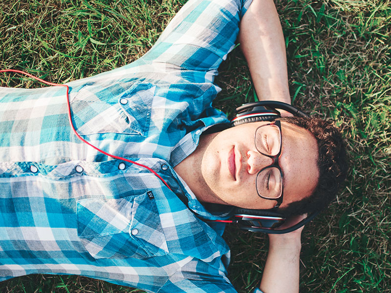 A guy lying in the grass and smiling as he listenings to songs about getting over someone on his headphones.