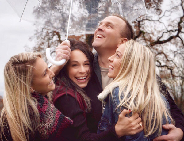 A group of people hugging and laughing under an umbrella showing some of these 3 types of love.