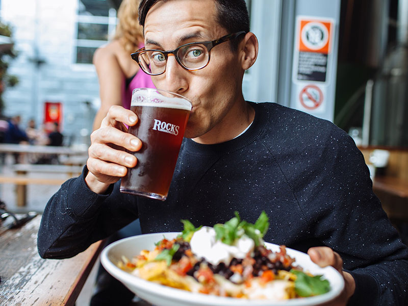 A man at a brewer, drinking a beer and holding some nachos as he takes advantage of one of these good date ideas.