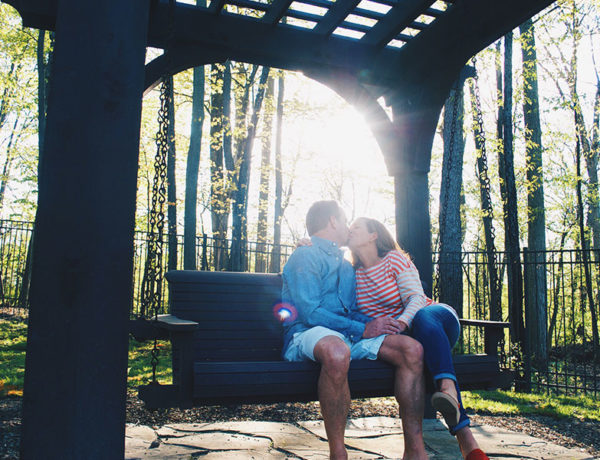 A couple who met on over 50 dating sites, kissing on a park bench as the sun shines through the trees.