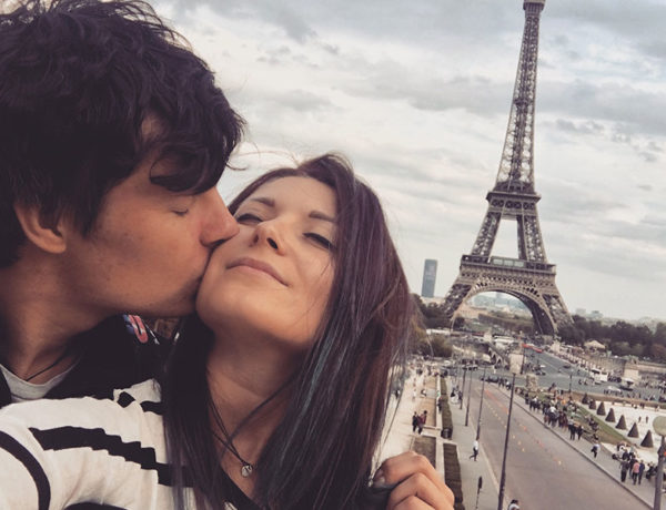 A couple who met international dating, kissing in front of the Eiffel tower.