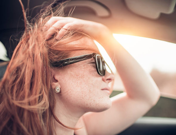 A woman who knows it's time to move on, driving in her car at sunset and thinking about her relationship.