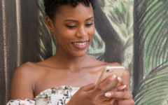 "A woman wondering, ""Should I text him first?"" while looking into her phone outside."