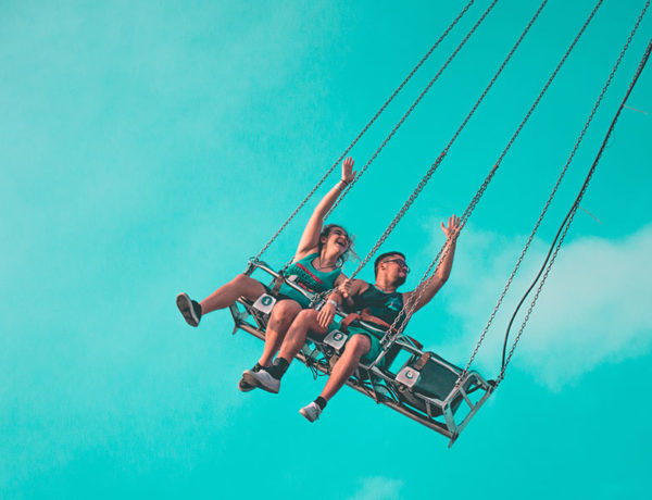 A couple on a amusement ride laughing and smiling on one of these best date ideas.