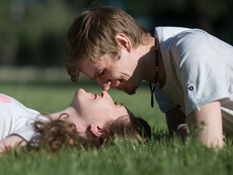 A woman wondering how to attract men, lying in the grass and looking up into the eyes of man flirting with her.
