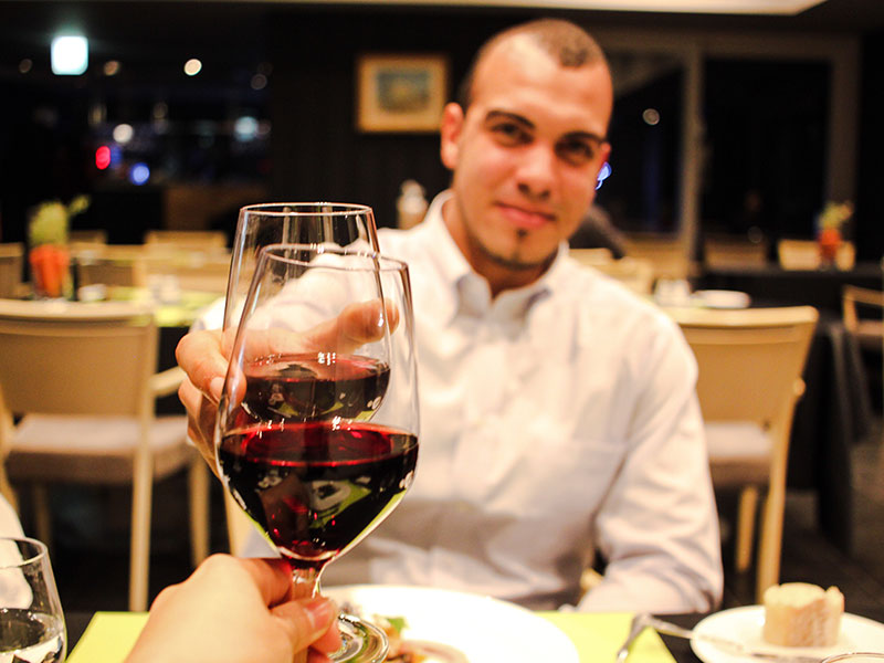 A guy on a first date cheersing his date across the table.