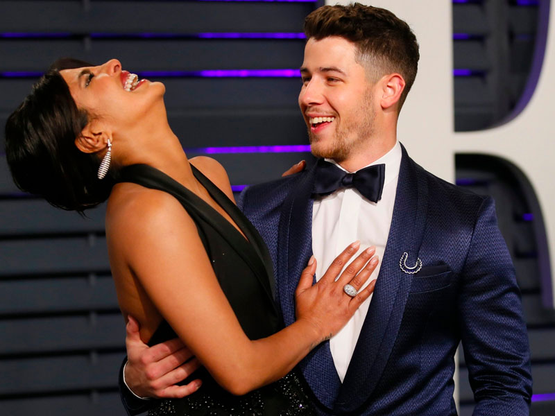 Nick Jonas and Priyanka Chopra, one example of an older woman dating younger men, laughing and hugging at a red carpet event.