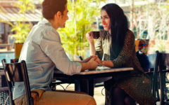 A couple at a table using one of these conversation starters for dating to chat about while they sip coffee.