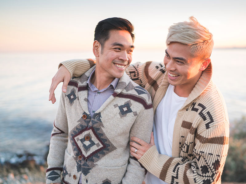 A gay couple on the beach laughing together as they take a photo for social media sites.