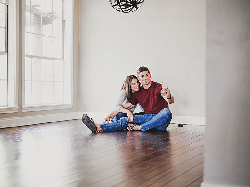 A couple moving in together taking a selfie on the floor of their new apartment.