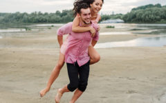 "A girl wondering ""does he like me"" smiling and laughing as a guy friend carries her on his back on the beach."