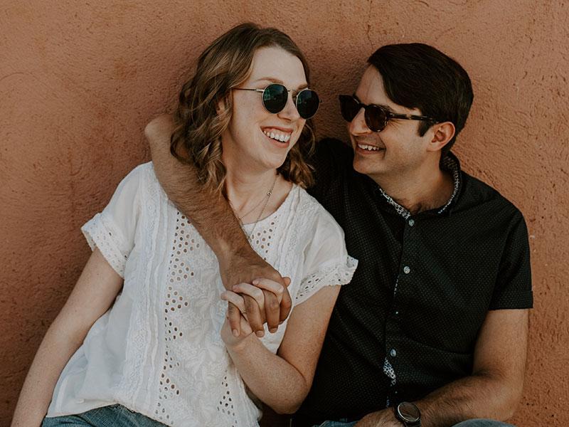 Une femme qui sait comment impressionner un mec souriant et flirtant avec son petit ami alors qu'il passe son bras autour d'elle.