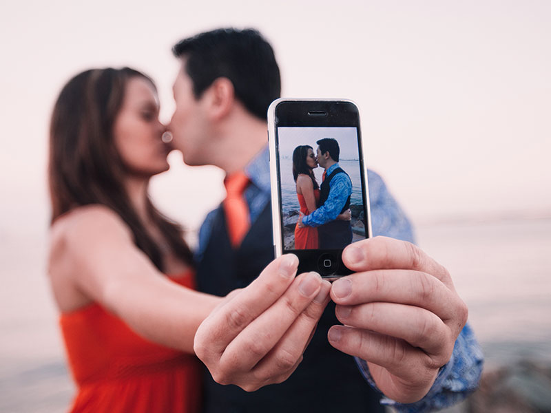 A couple taking a selfie while kissing, displaying an example of what social media and relationships.