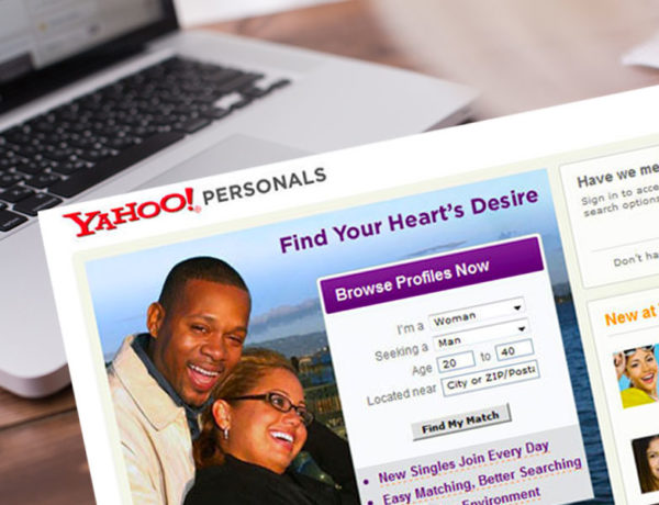 A screenshot of the Yahoo dating site in front of someone typing at their computer.