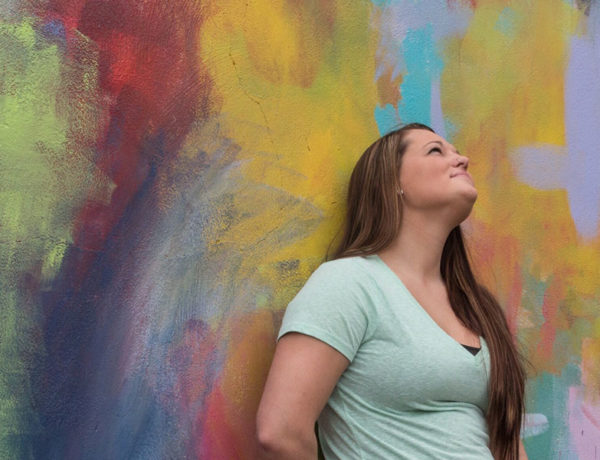 A women who's letting go for a relationship leaning against a wall looking up and smiling.