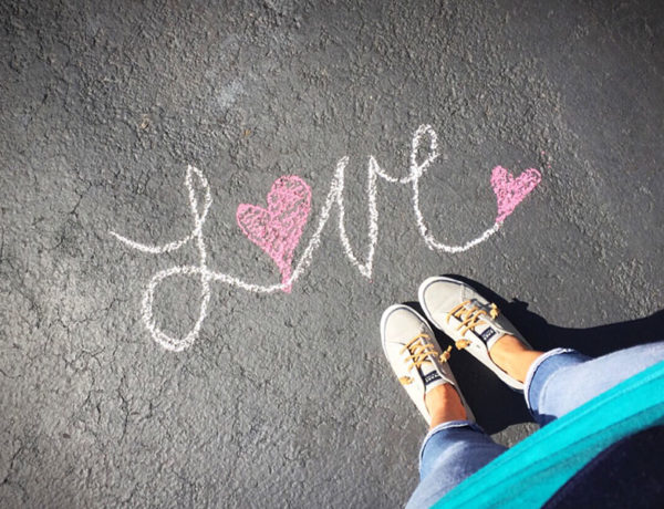 A girl looking down at her shoes and a single life quote that says love written at her feet.