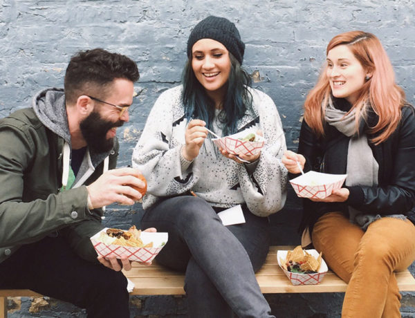 A group who learned how to find friends online laughing and eating together outside.
