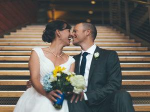 Un couple qui a appris quelque chose de ces vraies citations d'amour, assis sur les marches de l'église le jour de leur mariage, touche le nez et rigole ensemble.