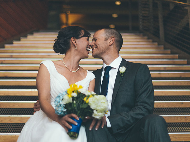 A couple who learned a thing or two from these true love quotes, sitting on the church steps on their wedding day touching noses and laughing together.