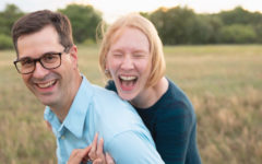 A man over 40 who's never been in a relationship before, laughing with his girlfriend in a field as he learns how to navigate his way through it.