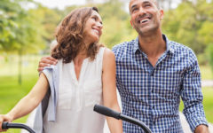 A couple dating over 40 laughing and smiling on their bikes together.