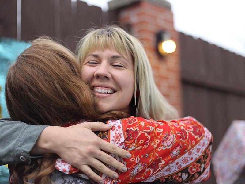 Deux amis qui savent que leurs amis vont et viennent, se serrant dans leurs bras et riant tout en se saluant.