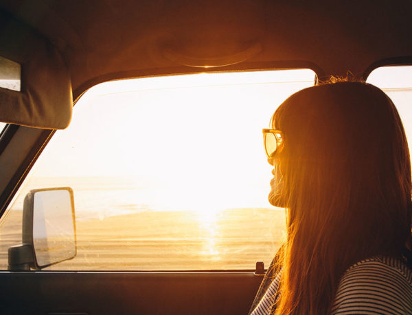 A woman who's getting over getting ghosted looking out the window of her car at the sunset.