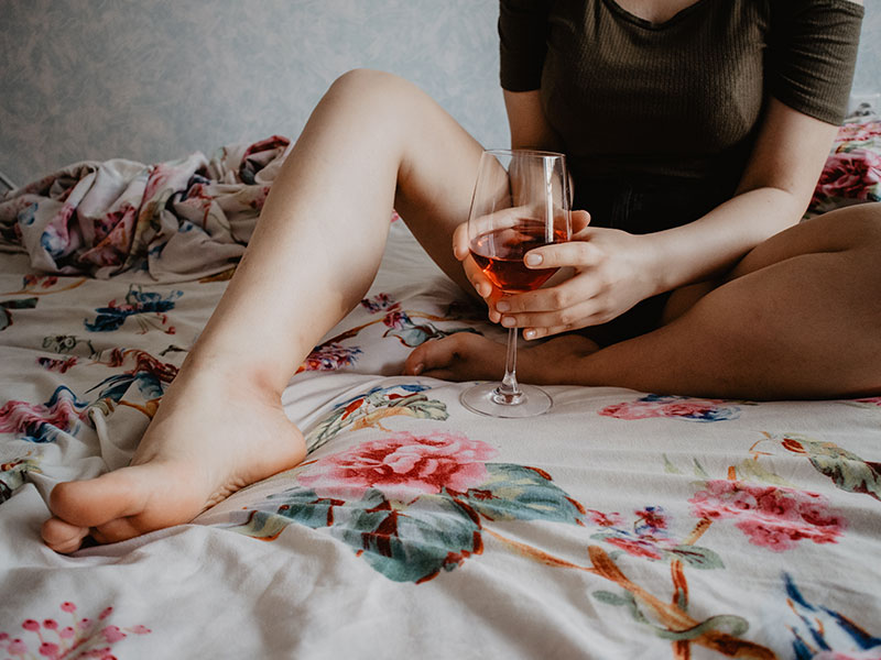 A woman who's alone on a Friday night, drinking wine in bed.