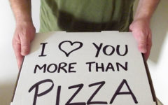 "A man holding a pizza box that says, ""I heart you more than pizza."" One of the romantic gestures for her that will make her day."