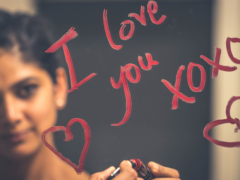 "A woman writing, ""I love you"" on a mirror with lipstick, one of the romantic gestures for him that guys appreciate."