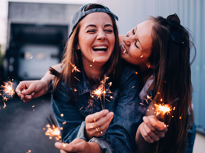Two BFFs who share friendship signs laughing while playing wish sparklers.