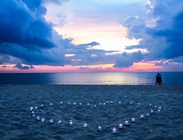 A couple kissing on the beach with a bunch of candles lit, one of the many ways to be romantic.