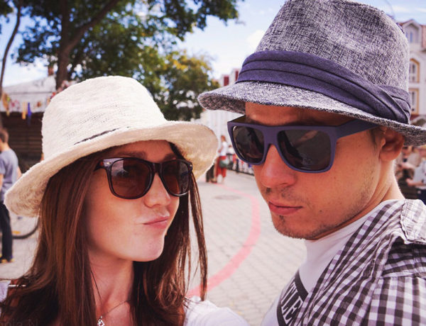 A girl with her guy best friend, making a funny face while wearing similar hats and sunglasses.