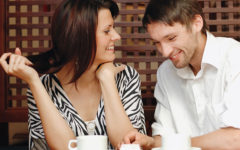 A man who took these flirting tips for guys, talking to a woman at a coffee shop who's laughing at his jokes.