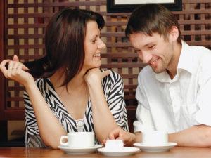 Un homme qui a pris ces astuces pour les gars flirter, parler à une femme dans un café qui se moque de ses blagues.