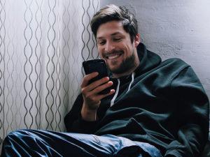 Un gars à la recherche d'applications plus doué que Tinder, souriant alors qu'il discute avec une fille sur une nouvelle application.