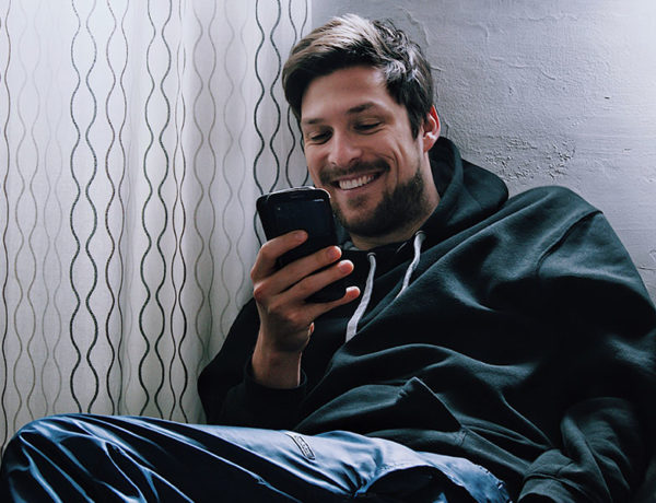 A guy looking for apps better than Tinder, smiling as he chats with a girl on a new app.